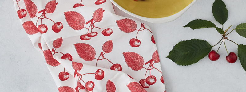 cherry cotton tea towel on a table with a bowl of cherries